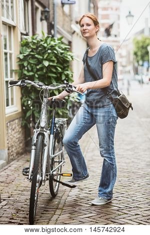 Woman Parking A Bicycle In Town
