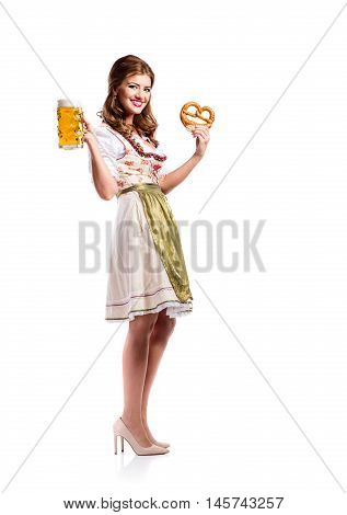 Beautiful young woman in traditional bavarian dress holding a mug of beer and pretzel. Oktoberfest. Studio shot on white background, isolated.