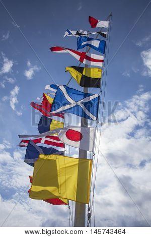 international maritime signal flags jn a flagpole against a blue sky