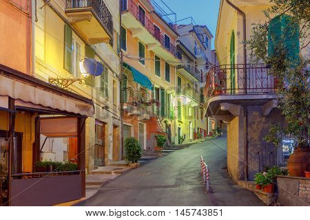 The old, narrow street in the medieval Italian village of Manarola at night. Parco Nazionale delle Cinque Terre, Liguria, Italy.