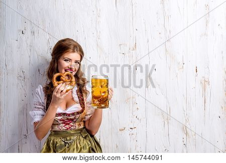 Beautiful young woman in traditional bavarian dress holding a mug of beer and pretzel, eating it. Oktoberfest. Studio shot on white wooden background. Copy space.