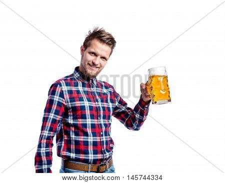 Handsome young hipster man in checked shirt holding a mug of beer, clinking. Oktoberfest. Studio shot on white background, isolated.