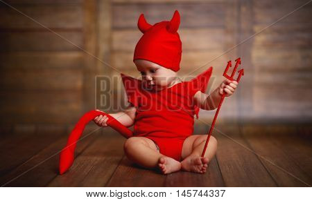 funny baby in devil halloween costume with horns and trident on a dark wooden background