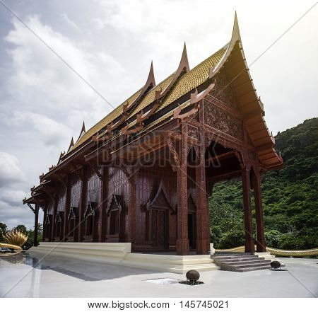 wide view of thai beautiful wooden temple,thai style carving of temple in prachuapkhirikhan province of Thailand,blue sky and cloud in background