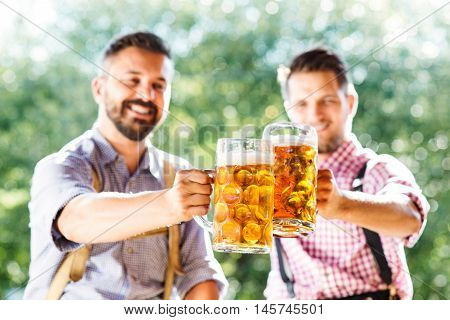 Two handsome hipster young men in traditional bavarian clothes holding mugs of beer, clinking. Oktoberfest. Sunny summer garden.