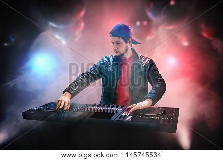 DJ (Disk Jockey) is mixing music in nightclub.