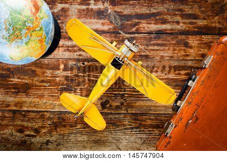 concept - time to travel plane, suitcase, globe on wooden table