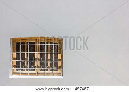 window with bars on a gray wall in clear day