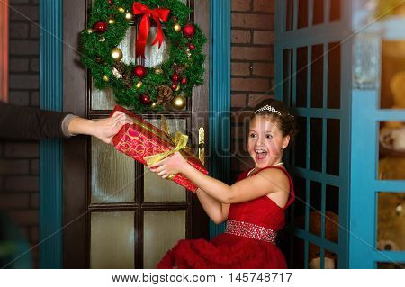 Little winter Princess in red dress accepts a Christmas gift from hands of giver. New year and Christmas celebration in enchanting holiday interior with decorated pine and Christmas wreath on door