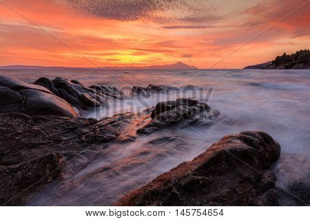 Vourvourou - Karidi beach with mount Athos in the background surprised at sunrise.