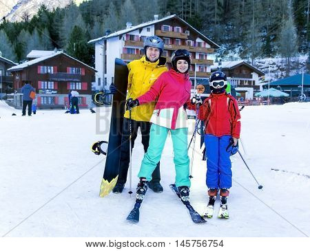 SWITZERLAND, SAAS-FEE, DECEMBER, 26, 2015 - Young active family enjoys winter sports in the charming Swiss resort of Saas-Fee, Switzerland