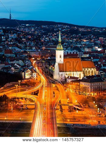 Aerial view of Bratislava Slovakia at night. Illuminated historical buildings with car traffic at the highway