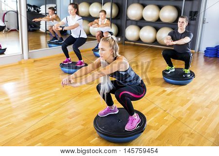 Dedicated people in workout team doing squats on half ball in a fitness gym class. Core muscle and balance workout. Teamwork and motivation.
