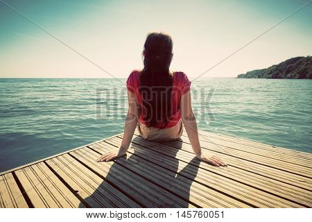 Young woman resting on a wooden jetty looking at the calm sea on sunny summer day. Vintage