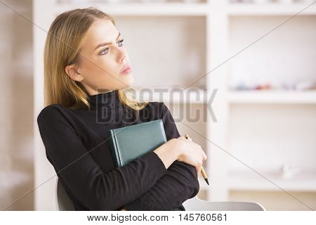 Businesswoman With Notepad Thinking At Workplace