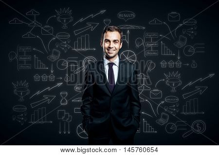 Confident smiling businessman in suit on dark background with business sketch. Success concept