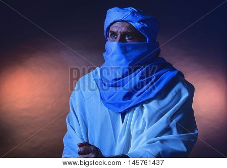 Berber Man In Night Light Wearing Blue Turban With White Robe. Leaning On Cane. Studio Shot.