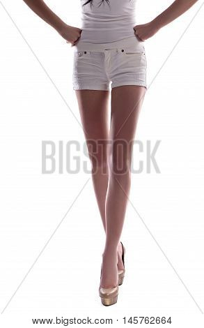 young woman in shorts on a gray background