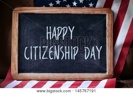 a chalkboard with the text happy citizenship day written in it and the flag of the United States, on a rustic wooden surface