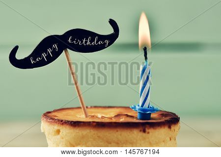 closeup of a cheesecake topped with a moustache with the text happy birthday written in it and attached to a stick, and a lit birthday candle against a rustic pale green wooden background