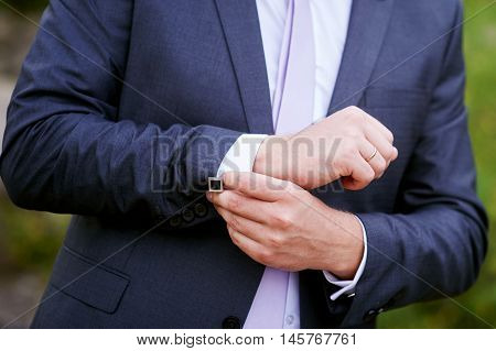 man in black jacket wears cuffs in park.
