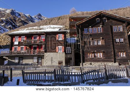 Traditional wooden old houses on a background mountains in the charming Swiss resort of Saas-Fee, Switzerland