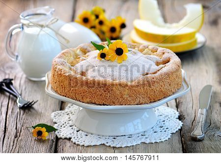 Sponge cake with melon on old wooden background.