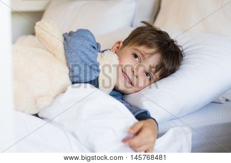 Young boy sleeping on bed. Cute little boy lying in bed and smiling in the morning time. Small boy hugging his teddy bear for his afternoon nap.