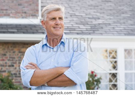 Successful happy retired man standing with crossed arm. Senior man thinking and looking away. Portrait of old man feeling good to retire.