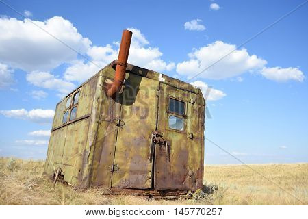 lonely old metal shed with windows and a pipe in a field with straw
