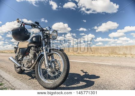 Life of biker. Cropped shot of motorcycle parking on road with helmet on handlebars