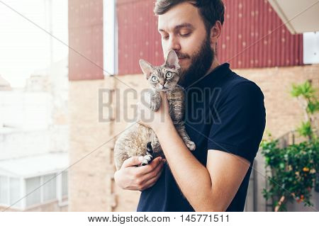 Happy young man is standing on a balcony with his cat. Home pets. Beautiful man is holding and hugging his cute curious devon rex cat