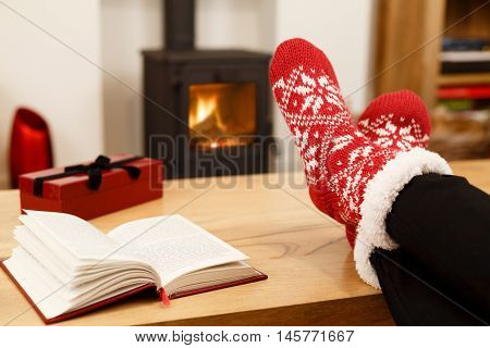 Woman relaxing at home in front of a cozy fire at Christmas