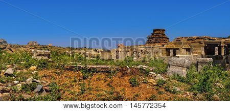 Tourist indian landmark Ancient ruins in Hampi. Beautiful nature scenery with bright blue sky and strange landscape with large rocks Hampi India