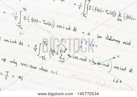 Maths homework showing handwritten mathematical formulae on paper