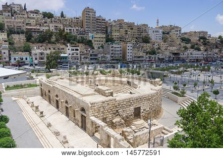 Amman, Jordan -May 28, 2016: Odeon - little roman amphitheatre in downtown with Amman cityscape background Amman Jordan