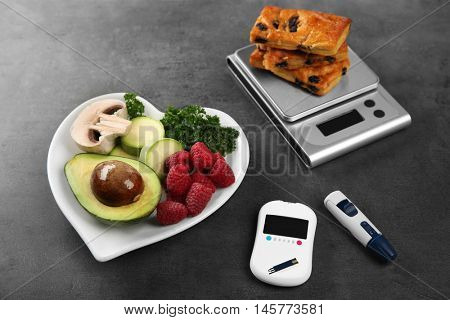 Glucose meter with healthy food and cookies on table