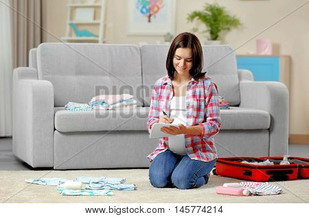 Pregnant woman making packing list for maternity hospital at home