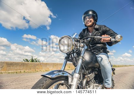 He is handsome biker. Cropped shot of biker guy in leather jacket on motorcycle looking on road and smiling