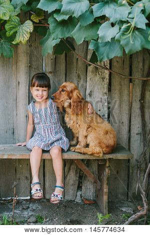 country girl sitting on a bench with her dog under vine. girl playing with her dog. wooden background.