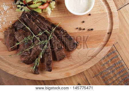 Skirt steak with salad and sauce. Wooden background
