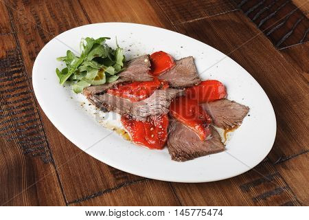 Baked roast beef with rucola and bell pepper in a white oval plate. Wooden background.