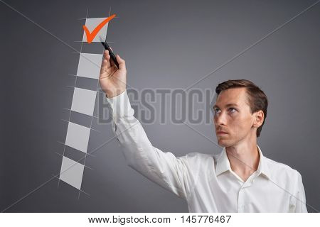 Young business man in white shirt checking on checklist box. Gray background.