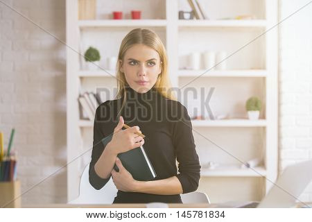 Female With Notepad Thinking At Workplace