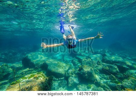 Young female snorkeling in tropical sea. Woman apnea swims in coral reef.