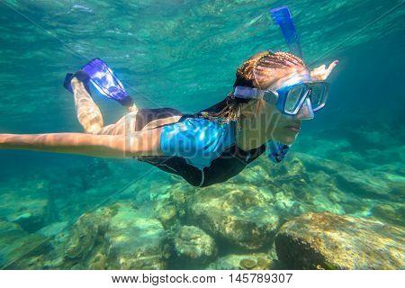 Close up of female apnea swims in tropical turquoise sea of Racha Noi, Phuket in Thailand.