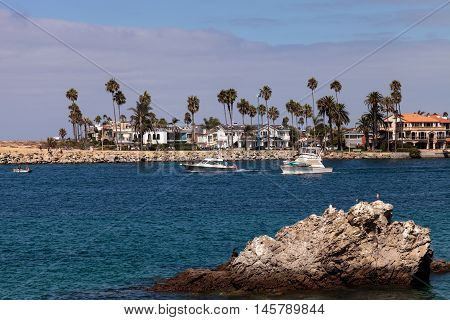 Boat leaving the harbor in Corona del Mar, California in summer