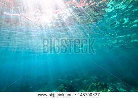 Underwater blue background with sunbeams and copy space.