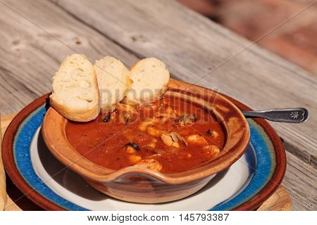 Seafood cioppino with French bread and shrimp, fish, clams, lobster, crab and scallops in tomato sauce in a pottery bowl on a dish and a cutting board.