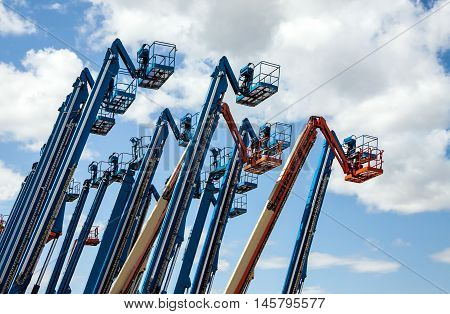 Rental construction  equipment. Boomlifts  with raised platforms are on-site on   for the equipment for rent.